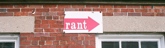 "Image of building with torn sign reading ""Rant"""