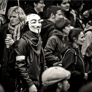 Image of protester wearing Guy Fawkes mask