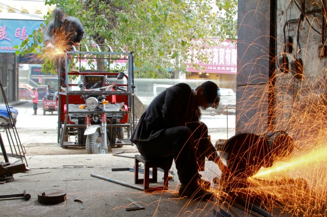 A father-son team work together in a workshop modifying three-wheeled vehicles in Guizhou, China.